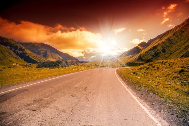 Straße in den Bergen gestalten mit hellem Sonnenuntergang landschaftlich stockfotos