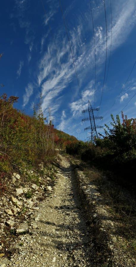 Straße in den Bergen, unter der Stromleitung stockfotografie