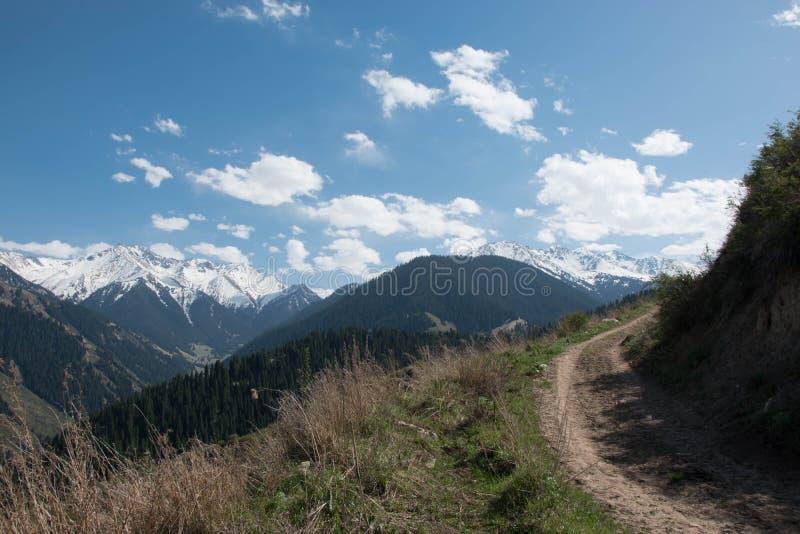 Straße in den schönen Frühlingsbergen, -wäldern und -himmel lizenzfreies stockbild