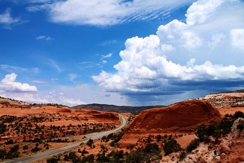 Straße, die durch gebogene, felsige Landschaft mit entfernten Sturmwolken in Utah, USA überschreitet stockfoto