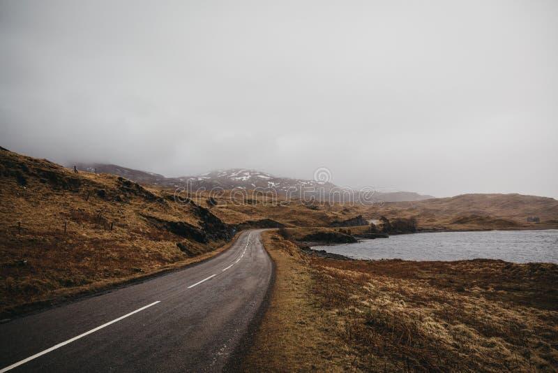 Straße, die schottische Hochländer nahe Lochinver durchläuft stockfotografie