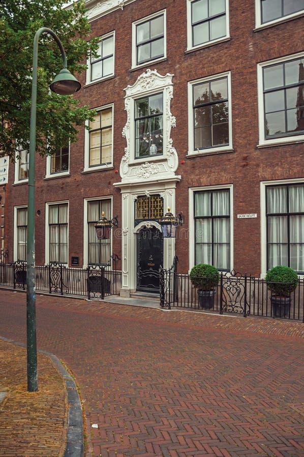 Straße mit Fassaden- und Eingangstor des eleganten Backsteinbaus am bewölkten Tag in Delft stockbild
