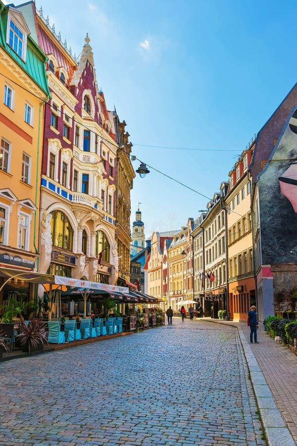 Straße mit Leuten und Helm des Stadtrates Riga lizenzfreie stockbilder