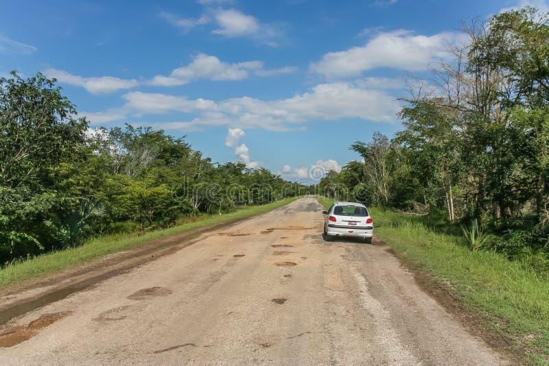 Straße mit Schlaglöchern im backcountry von Kuba stockbild
