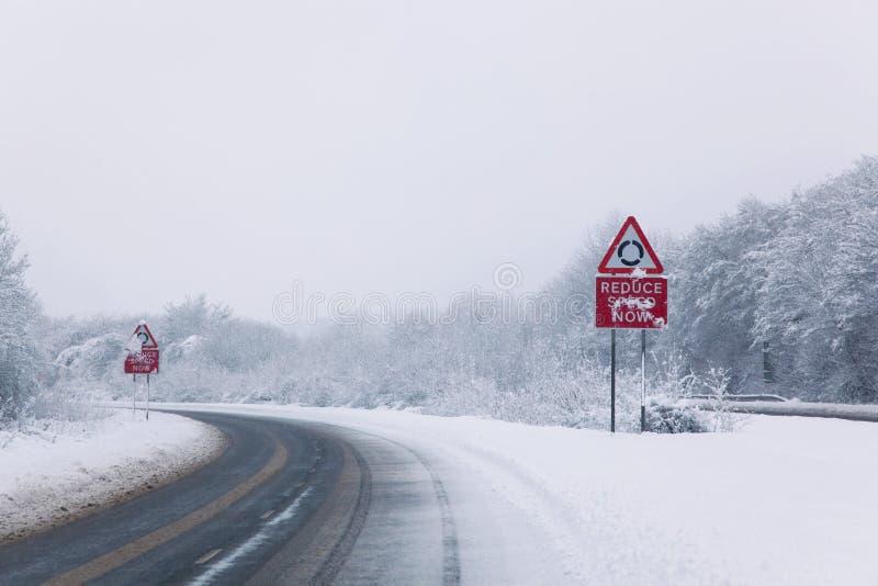 Straße mit verringern Drehzahl kennzeichnen jetzt während des Schneefalles lizenzfreies stockfoto