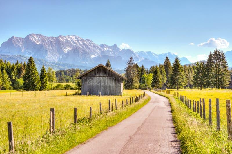 Straße und eine Scheune in den bayerischen Alpen stockfotos