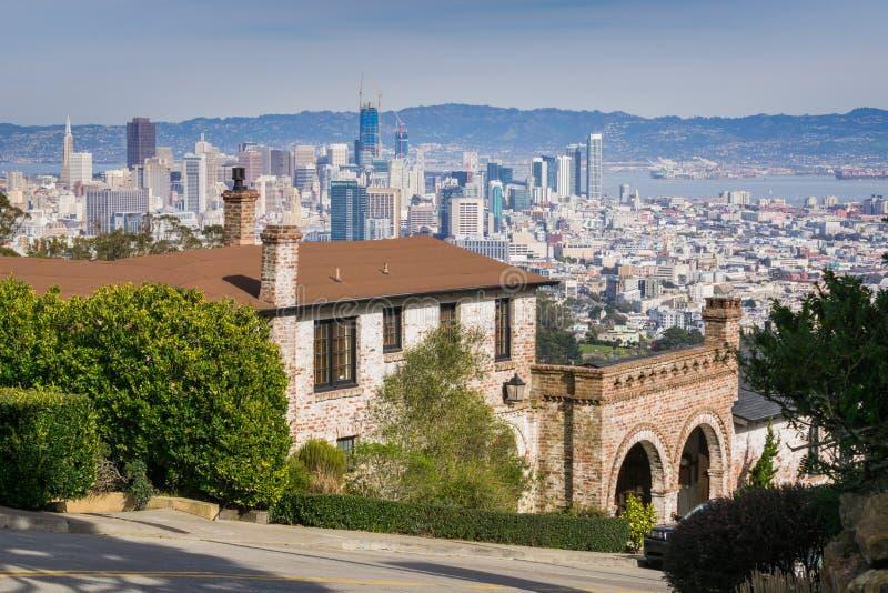 Straße und Häuser im Wohngebiet von San Francisco; im Stadtzentrum gelegene Stadtansichten in den Hintergrund, Kalifornien stockfotografie