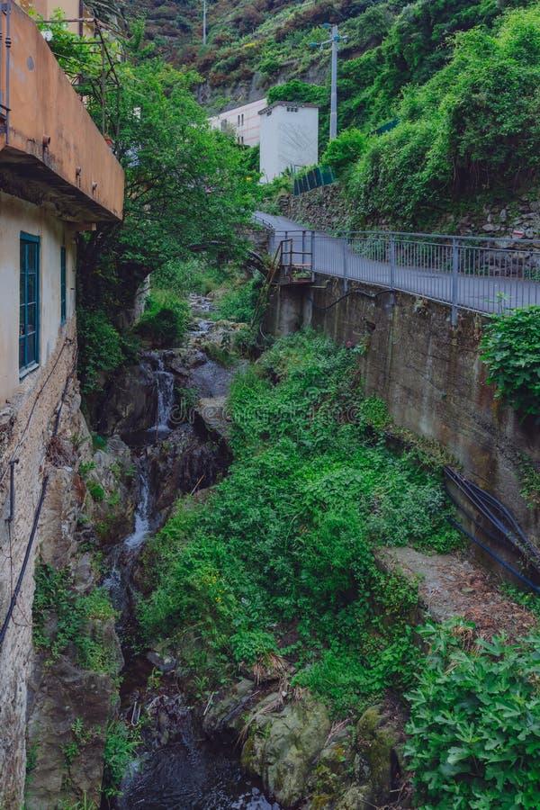 Straße und Haus durch Nebenfluss in Manarola, Cinque Terre, Italien stockbilder