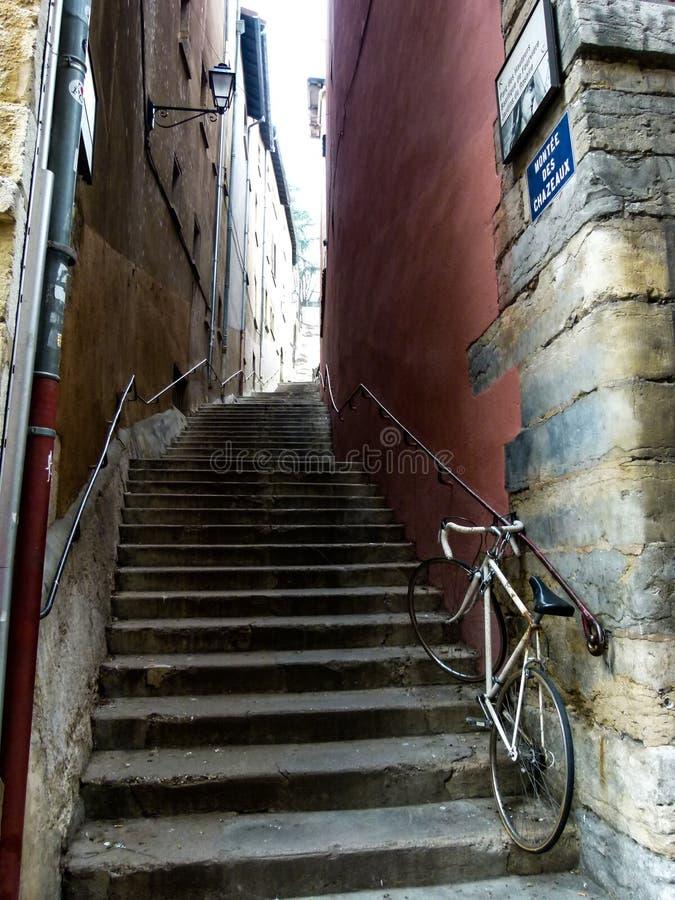 Straße von Lyon als Treppenhaus, das zwischen zwei alten Häusern mit einem alten Fahrrad im Vordergrund, Frankreich führt stockfotografie