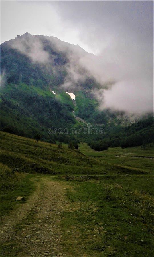 Straße zu einem Berg mit Wolken lizenzfreie stockbilder