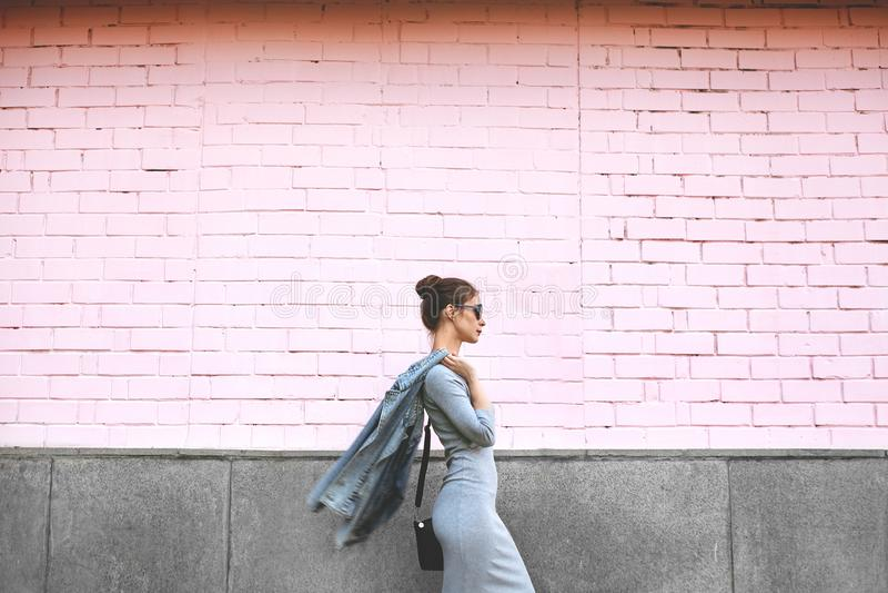 Straßen-Art-Trieb-Frau auf rosa Wand Swag-Mädchen-tragende Jeans-Jacke, graues Kleid, Sunglass Mode-Lebensstil im Freien lizenzfreie stockfotos