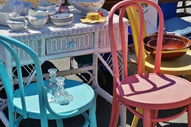 Straßen-Ausfallungs-Ramschverkauf-Weinlese-Antiken-Teller auf Weidenschreibtisch nahe bei bunten hölzernen hell gemalten Stühlen lizenzfreie stockfotos