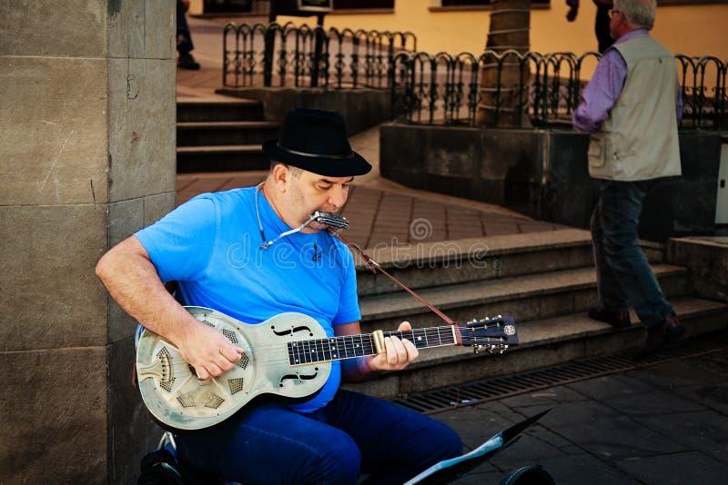 Straßen-Musiker, der Blau in der Straße spielt stockfoto