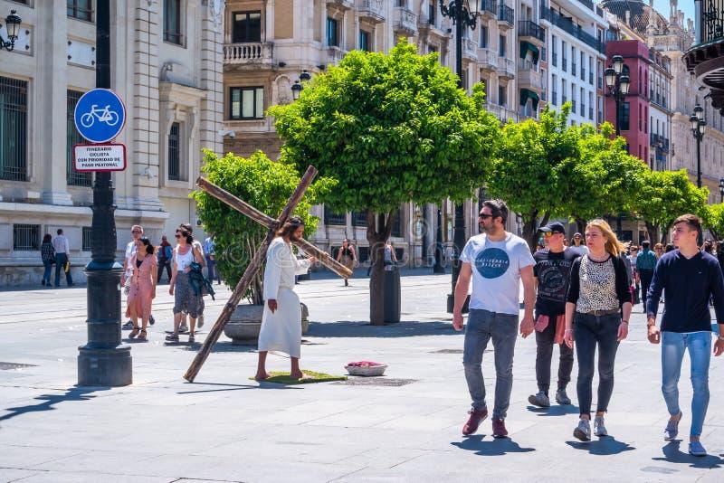 Straßen-Schauspielerspiel Jesus Christ Sevillas, Spanien am 8. Mai 2019, der großes hölzernes Kreuz trägt stockfoto