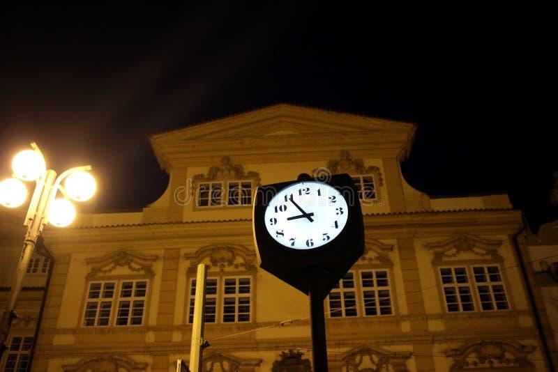 Straßen-Uhr in der Nacht gegen undeutliches Gebäude stockbild
