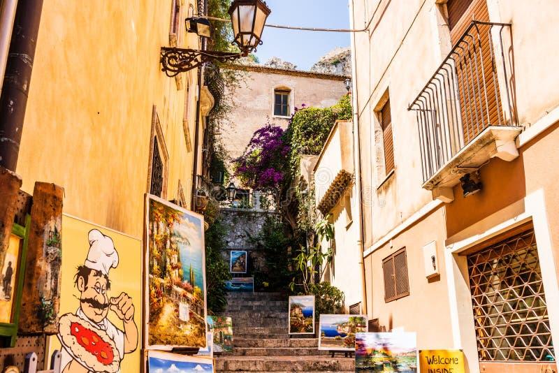 Straßenansicht der berühmten touristischen alten Stadt Taomina in Sizilien Malereien im Verkauf auf der Treppe lizenzfreie stockfotos