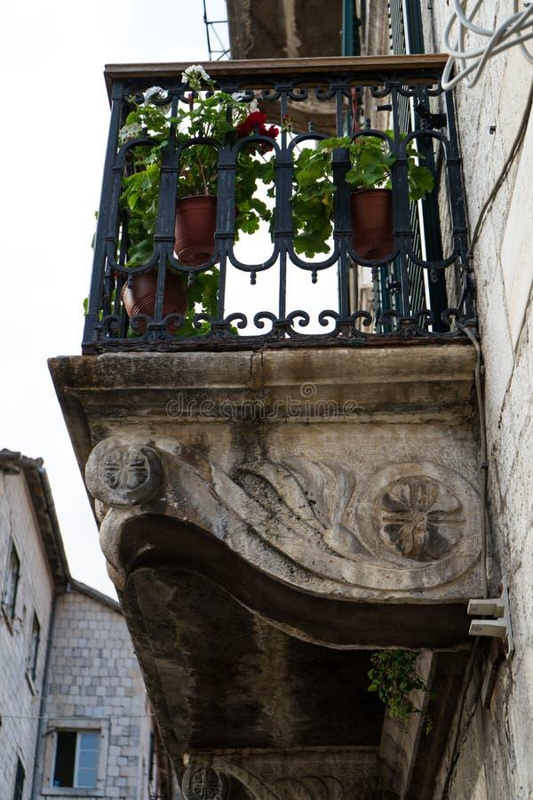 Straßenansicht einer recht Steinhausfassade mit einem kleinen Balkon mit einem Schmiedeeisengeländer und -Topfpflanzen Kotor, Mon stockbilder
