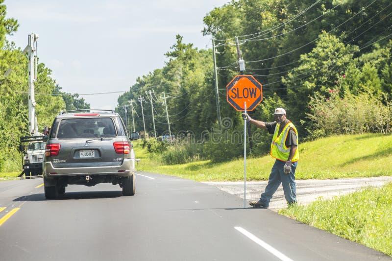 Straßenarbeitskraft zeigt langsames Zeichen stockfotos