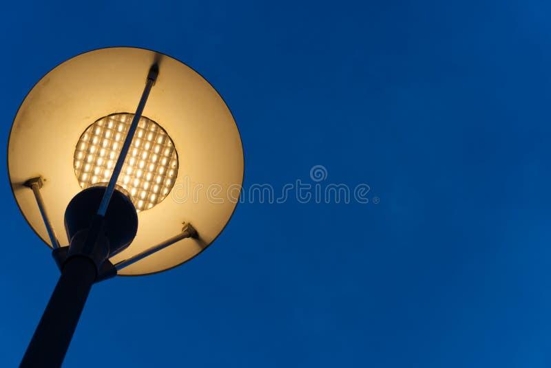 Straßenbeleuchtung oder der Laternenpfahl sind in der Nacht mit undeutlichem blauem Hintergrund glänzend stockbilder