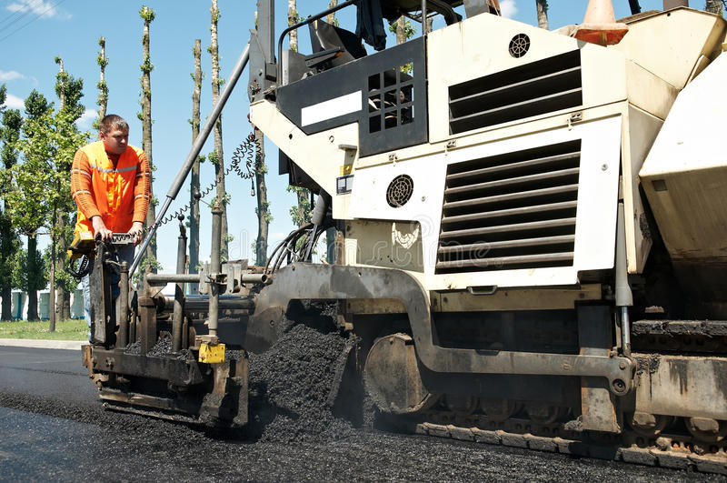 Straßenbetoniermaschinearbeitskraft bei den asphaltierenarbeiten lizenzfreies stockfoto