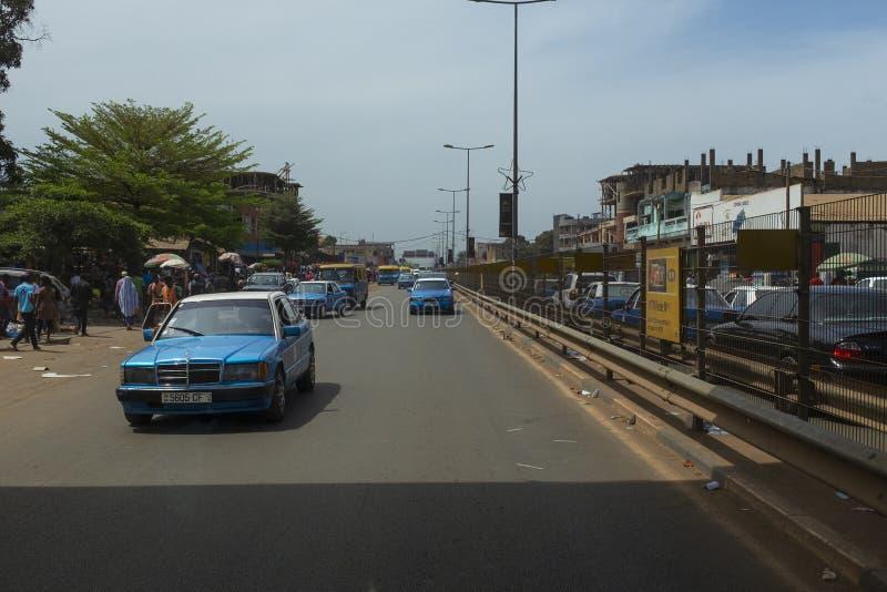 Straßenbild in der Stadt von Bissau mit Autos in einer Allee nahe dem Bandim-Markt, in Guinea-Bissau lizenzfreie stockfotos