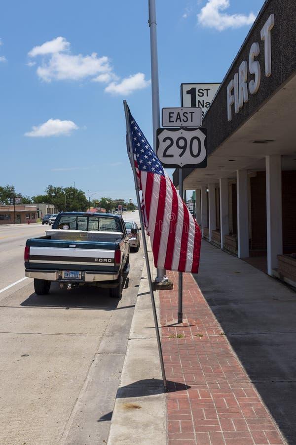 Straßenbild in der Stadt von Giddings entlang der Landstraße 290 mit einem Parkkleintransporter und der amerikanischen Flagge in  lizenzfreies stockbild