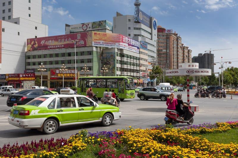 Straßenbild in der Stadt von Kaschgar mit Fahrzeugen an einem Karussell, Xinjiang, China lizenzfreie stockbilder