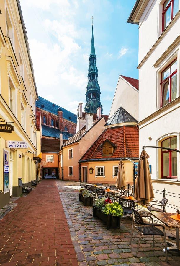 Straßencafé und Helm des Heiligen Peter Church Riga lizenzfreie stockfotos