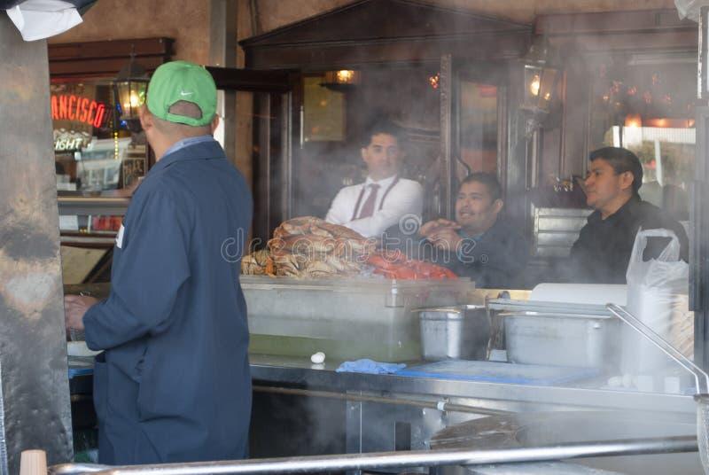 Straßencafékoch und -besucher schließen oben Mann, der Krabben in einem Straßencafé kocht lizenzfreie stockfotografie