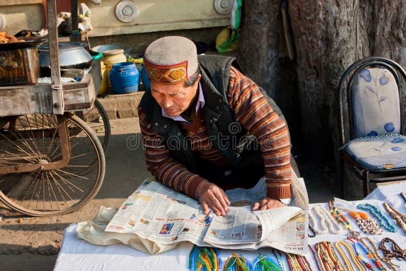 Straßenhändler im orientalischen Kleid liest die Zeitung lizenzfreies stockfoto