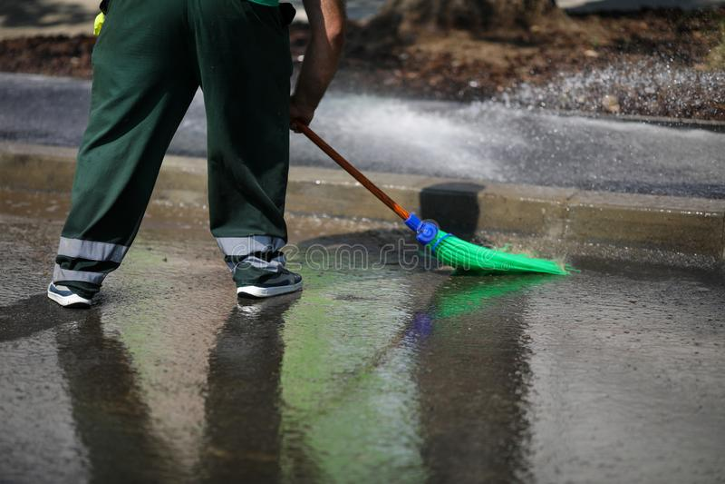 Straßenkehrer reinigen Stadtrundgang mit Wasser aus einem Schlauch und einem Plastikbrot - Arbeiten mit blauem Kragen stockfoto