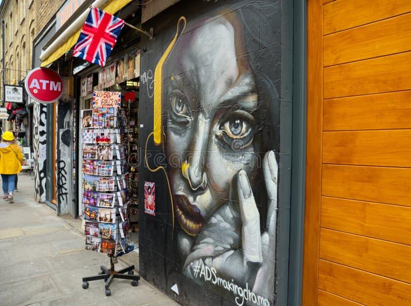 Straßenkunst das Porträt der Frau u. Postkartentourismusgeschäft stockfotos