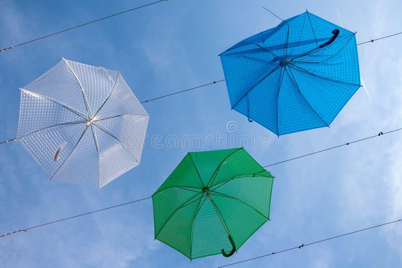 Straßenkunst mit den blauen, grünen und weißen Regenschirmen Hängens stockfotos