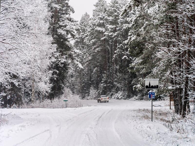 Straßenkurve und verlassen Auto im Winterwald lizenzfreie stockbilder