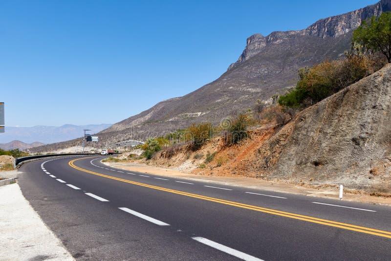 Straßenkurve zwischen den felsigen und trockenen Bergen am Mittag und klarem Himmel stockfotografie