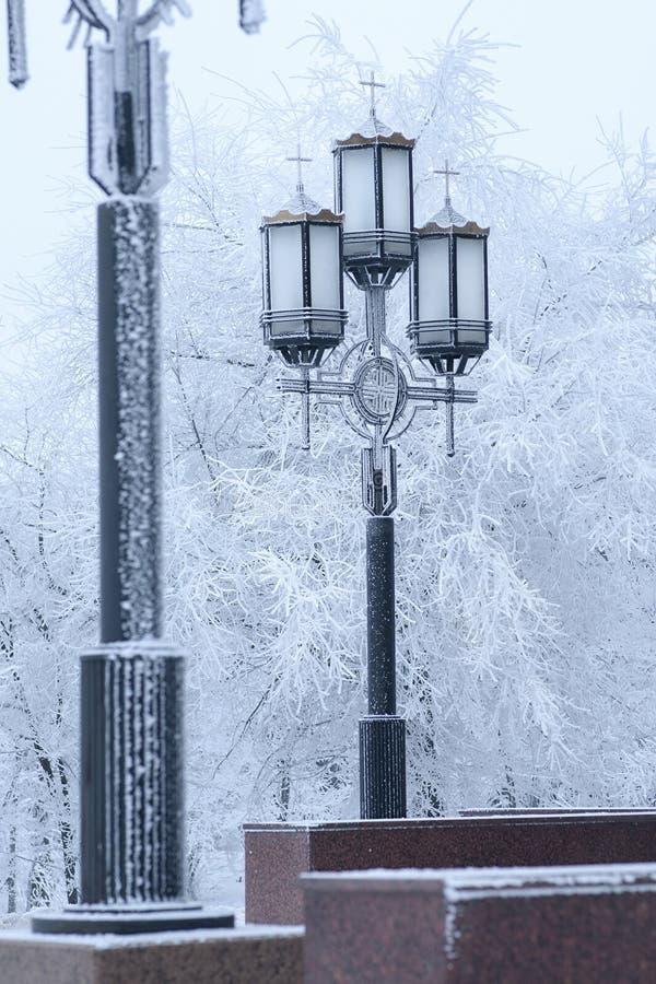 Straßenlaterne in der schneebedeckten Straße des Winters stockbild