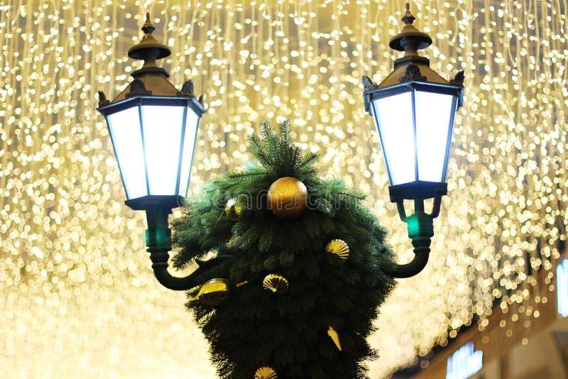 Straßenlaterne und Weihnachtsdekorationen unter hellen Lichtern lizenzfreie stockfotografie