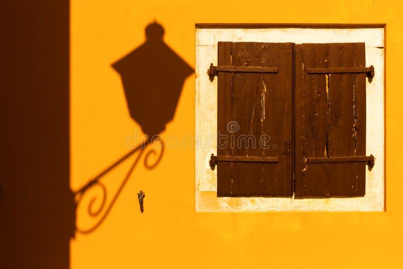 Straßenlaterneschatten auf einer gelben Wand stockfotografie
