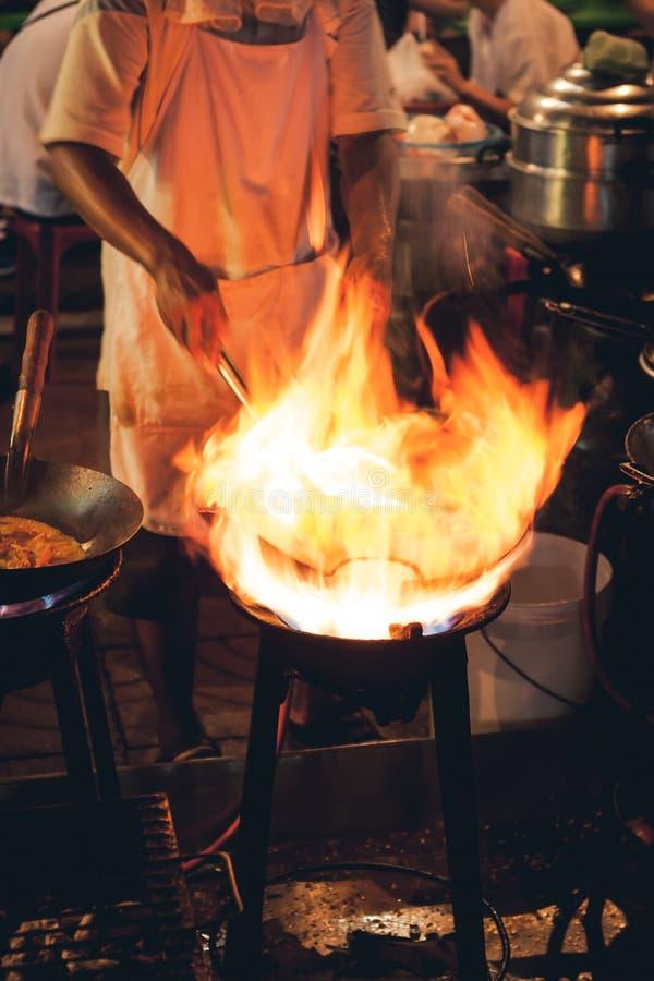 Straßenlebensmittelchef, der Fleisch und Fische in einer Wanne mit Feuer und Flammen unter ihm kocht Chinatown, Bangkok, Thailand lizenzfreie stockfotografie
