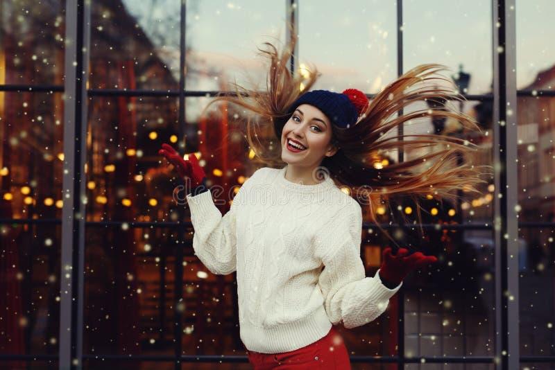 Straßenmodeporträt der lächelnden schönen jungen Frau, die mit ihrem langen Haar spielt Dame, die den klassischen Winter gestrick lizenzfreie stockfotos