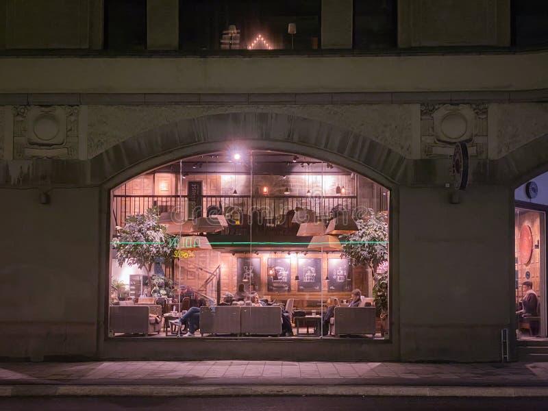 StraßenNachtsicht in ein Café mit Blick von außen durch ein Fenster stockfoto