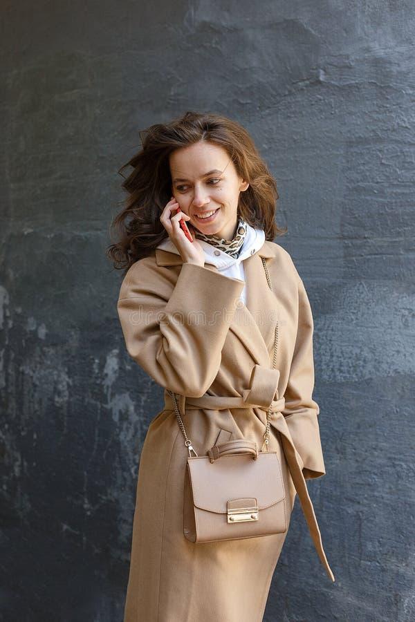 Straßenporträt der jungen lächelnden Frau, die beige Mantel unter Verwendung des Handys trägt stockfotografie