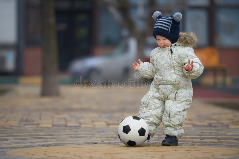 Straßenporträt des kleinen Jungen, der Fußball spielt stockfotografie