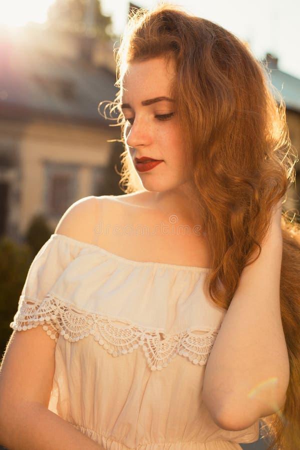Straßenporträt des recht redhaired Modells mit dem langen wellenartig bewegenden Haar stockfoto
