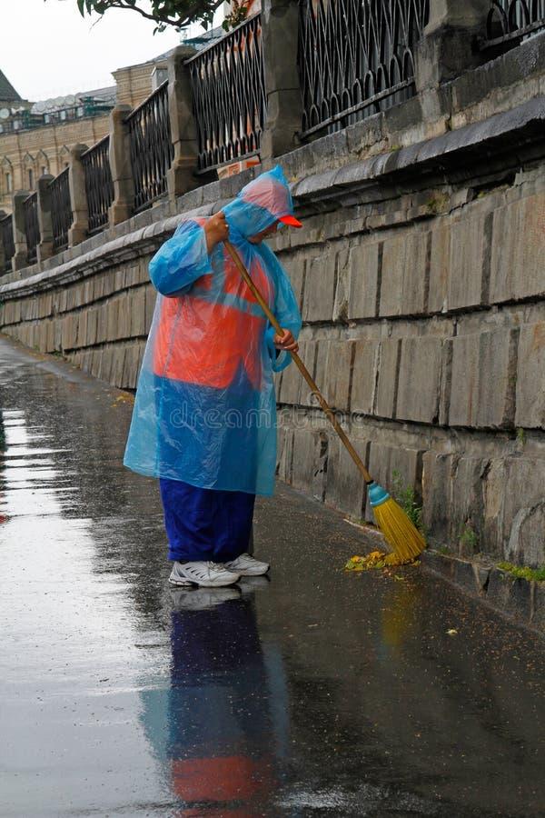 Straßenreiniger arbeitet mit einem Besen an einem regnerischen Tag in Moskau lizenzfreies stockfoto