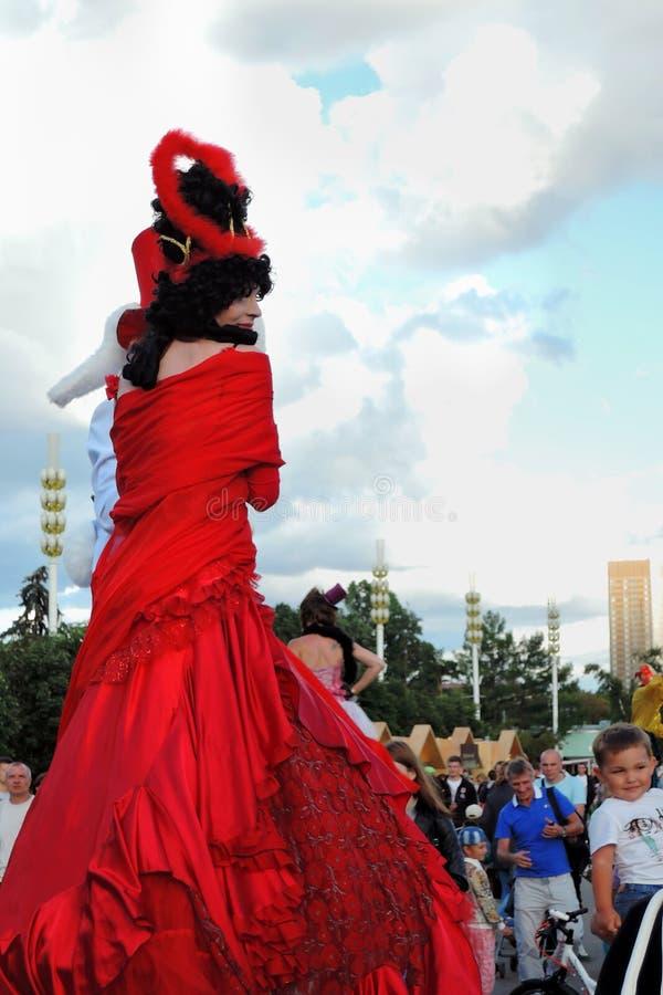 Straßenschauspielerfrau wirft für Fotos im roten Kleid auf lizenzfreies stockbild