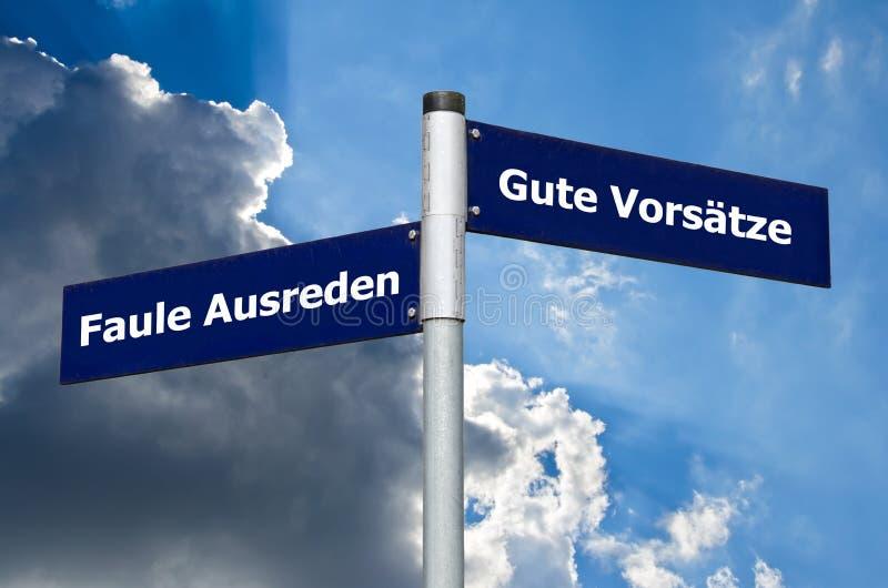 Straßenschild, das Wahl zwischen 'lahmen Entschuldigungen und 'dem Text des neuen Jahres oder der guten Beschlüsse auf Deutsch sy lizenzfreies stockbild