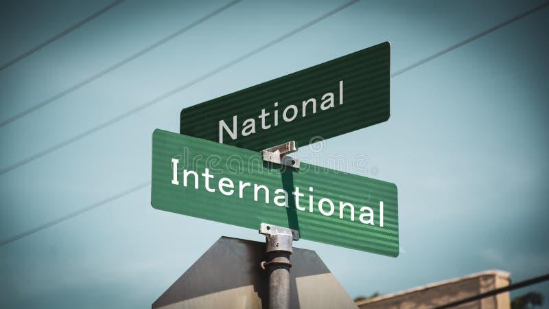 Straßenschild international gegen nationales stockfotos