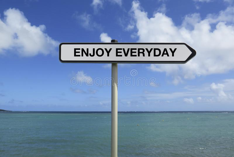 Straßenschild mit ENJOY EVERYDAY-Text unter Karibik siehe Hintergrund stockfotografie