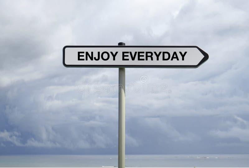 Straßenschild mit ENJOY JEDEN TAG Text unter bewölktem tropischem Himmelshintergrund lizenzfreies stockfoto